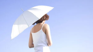 Woman holding umbrella to prevent sun and skin cancer