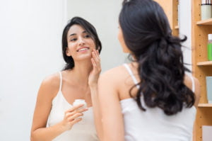 Woman applying sunscreen to prevent sun spots